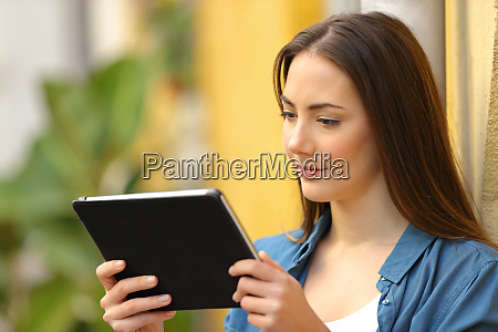 serious woman watching media on tablet
