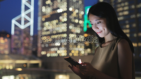 woman text on cellphone at night