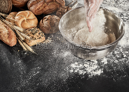 baker dusting his dough with flour