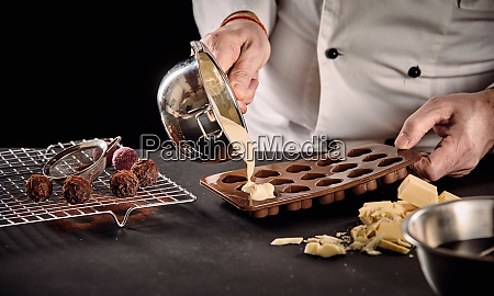 chef or chocolatier pouring melted white
