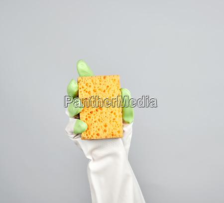 gloved hand holds yellow kitchen sponge