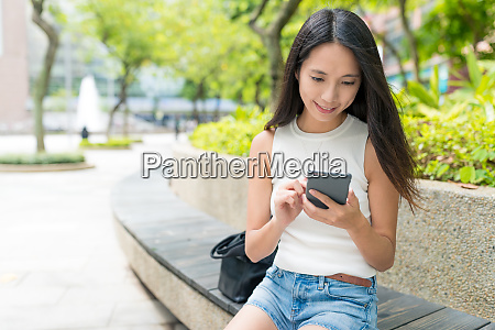 woman sending text message in city