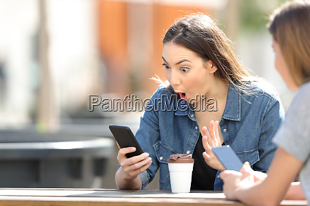 surprised woman checking phone online content