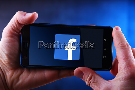 hands holding smartphone displaying logo of