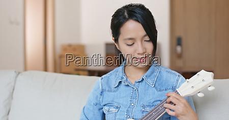 woman enjoy play with ukulele