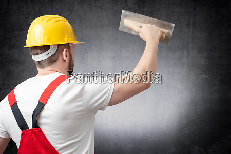 rear view of a worker plastering