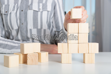 woman placing last piece to wooden