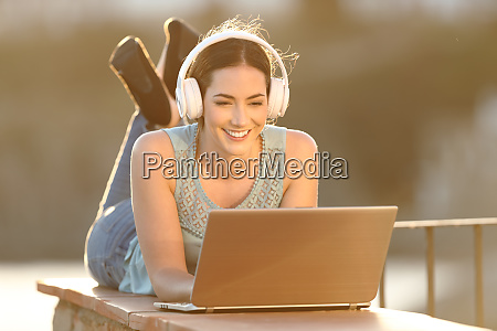 happy woman with headphones watching media