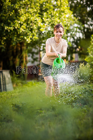 pretty middle aged woman watering plants