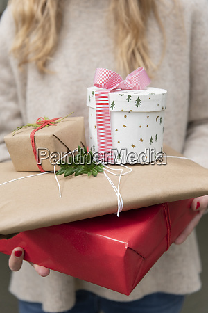 hands of woman holding christmas presents