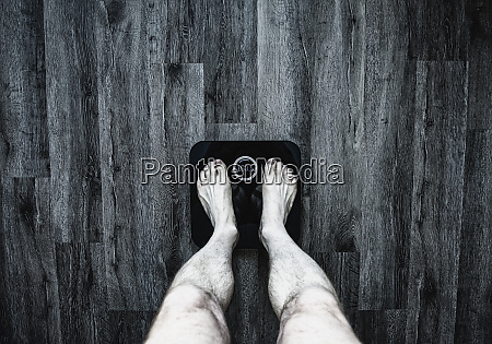 legs of man using weight scale