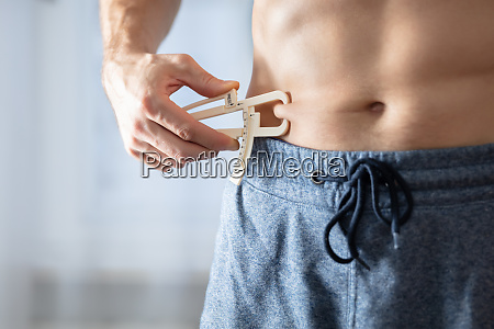 person measuring his body fat with