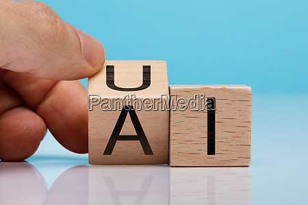 persons hand holding wooden block with