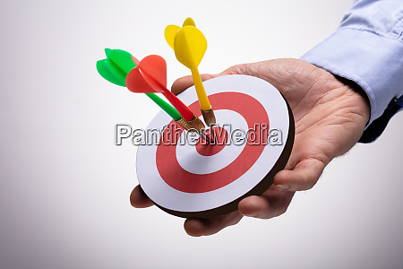 human hand holding colorful darts on