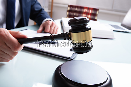 male judge hands holding mallet and