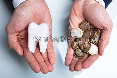 man holding tooth and golden coins