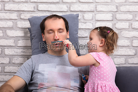 girl painting fathers face with color