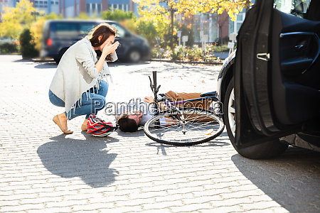 woman looking at unconscious male cyclist