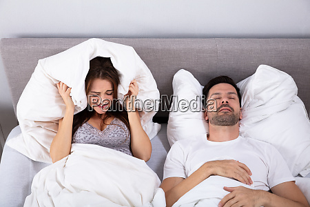 woman covering her ears while man