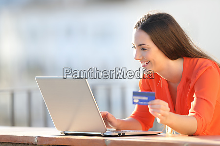happy woman buying online with laptop