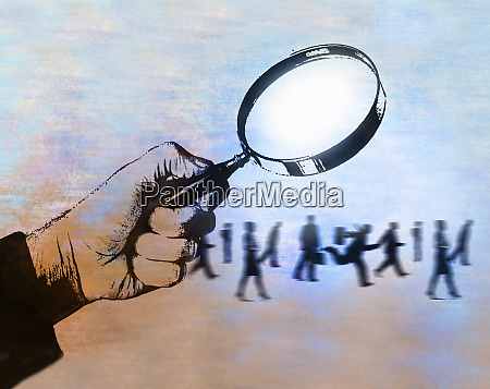 man examining business people under magnifying