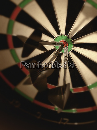 three darts hitting bulls eye on