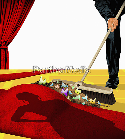 man sweeping the dirt under the
