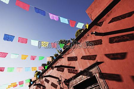 multicolour banners against blue sky san