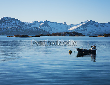 fishing boat by snow covered mountains