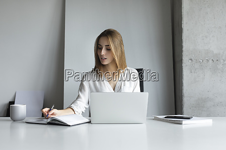 young businesswoman writing notes while working