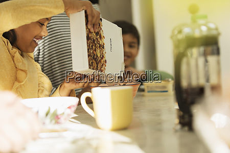 girl pouring breakfast cereal into bowl