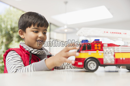 boy playing with fire engine toy