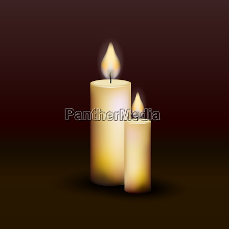 two burning candles on a dark