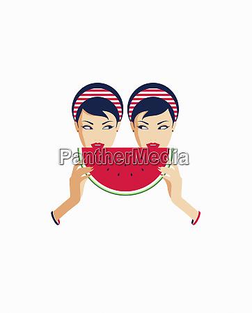 twin women sharing slice of watermelon