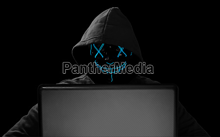 hacker with glowing mask behind notebook