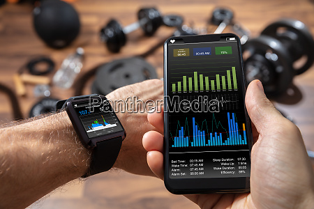 mans hand with mobile and smartwatch
