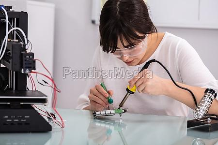 female technician using soldering iron
