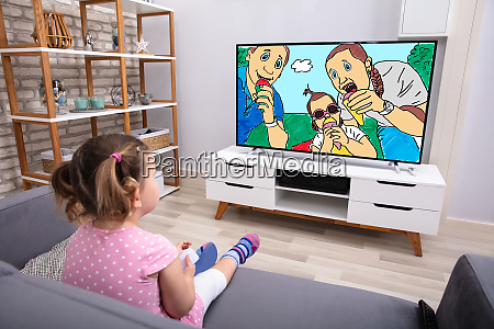 little girl sitting on sofa watching