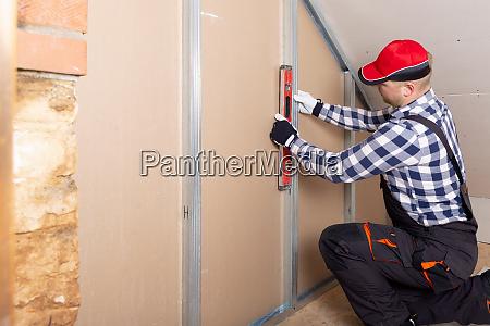 man holding level against plasterboard interior