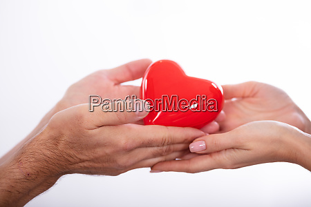 man giving heart on womans hand