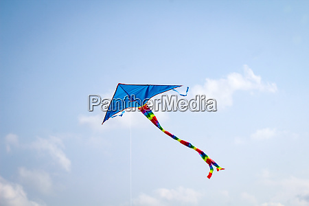 a kite rises in strong wind