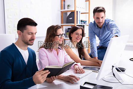 businessman showing information on computer to