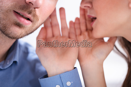 woman whispering secret to handsome man