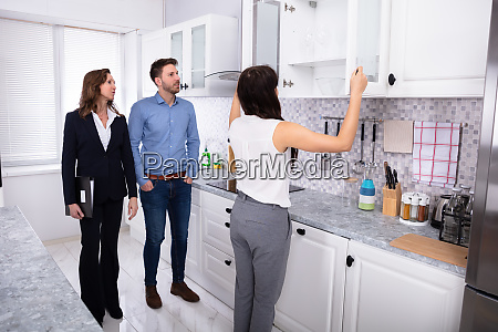 woman checking kitchen cabinet