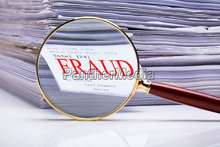 magnifying glass on fraud text near
