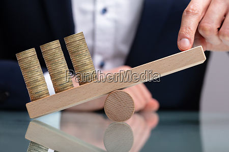 businessman balancing stacked coins with finger