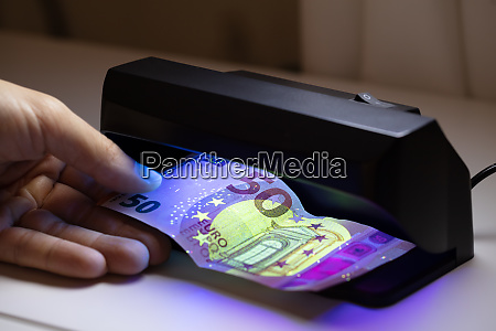 person checking banknote through the currency