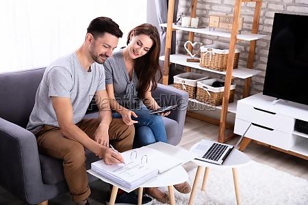happy couple calculating invoice