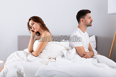 despaired married couple sitting on bed