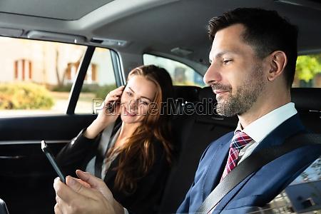 businesswoman sitting inside car beside her